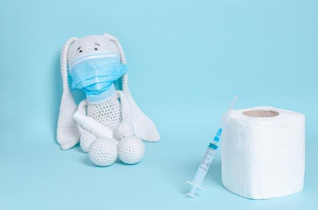 Papel higiênico e seringa, coelho de brinquedo macio infantil em uma máscara médica protetora detém um anti-séptico para as mãos sobre uma superfície azul