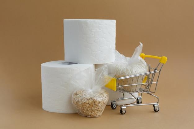 Papel higiênico e vários cereais em pequenos sacos plásticos em um carrinho de supermercado em uma superfície marrom. arroz e aveia