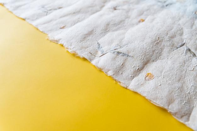 Papel japonês amassado close-up (washi) em papel amarelo na proporção de um terço. fundo de textura de papel com espaço de cópia.