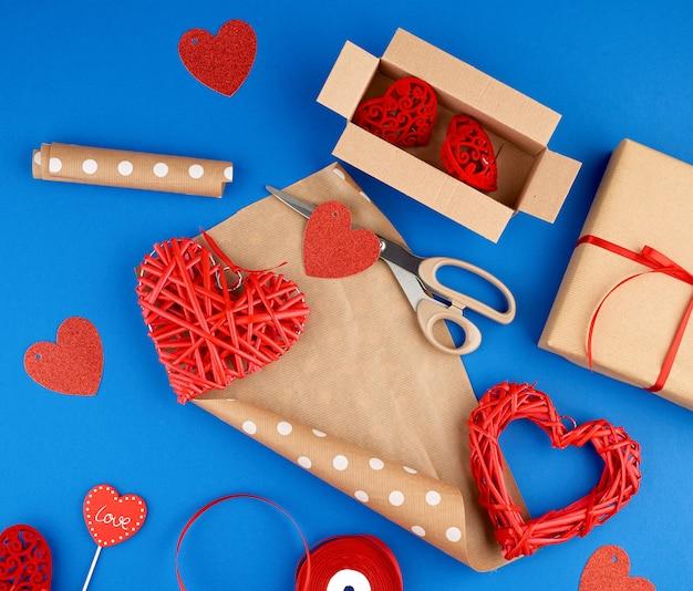 Papel kraft marrom, caixa de presente embalada, fita vermelha, coração vermelho, conjunto de itens para fazer presentes