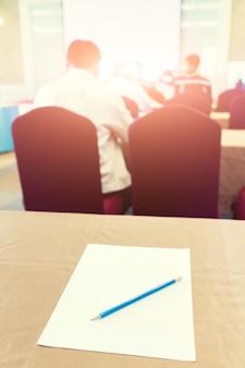 Papel, lápis sobre a mesa no fundo da sala de seminário