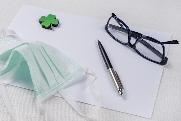 Papel limpo, uma folha de trevo verde e uma máscara protetora