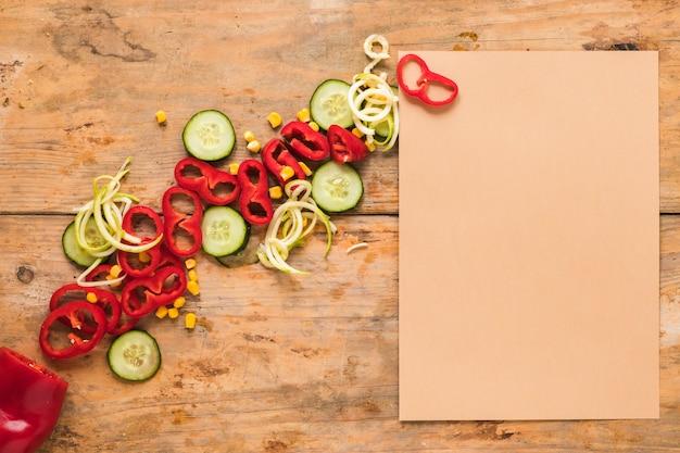 Papel marrom em branco além de páprica de fatia; pepino e milho na mesa de madeira