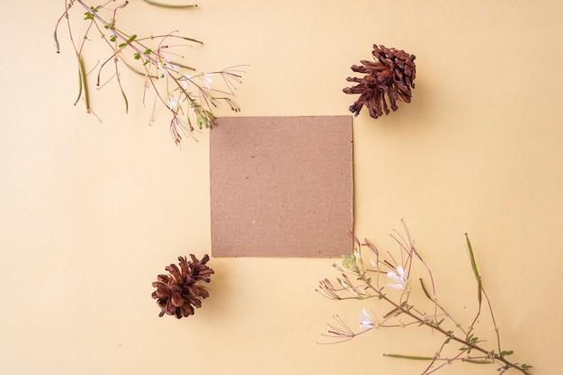 Papel marrom em um fundo amarelo pastel decorado com flores e pinheiros. cartão de visitas. cartão de visita, livro branco. modelos de papel. fundo de cor pastel