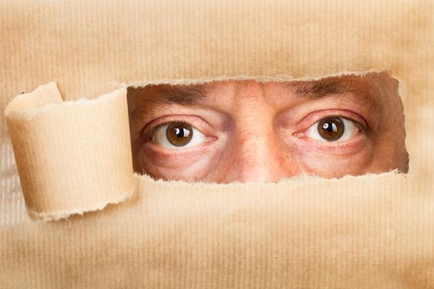 Papel marrom rasgado com um buraco e olhos de homem olhando através dele