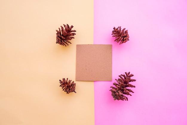 Papel marrom sobre fundo de papel pastel de duas cores rosa e amarelo com decoração de flores de frutas de árvore do abeto. cartão de visitas. cartão de visitas