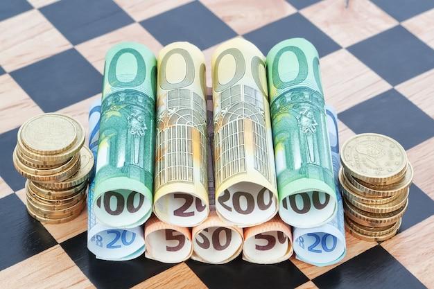 Papel moeda e moedas como o euro no tabuleiro de xadrez. imagem do conceito.