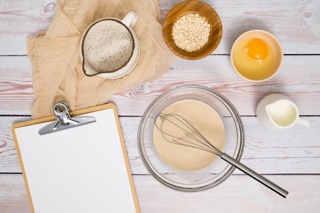 Papel na prancheta com farinha; gema de ovo; farelo de leite e aveia na mesa de madeira