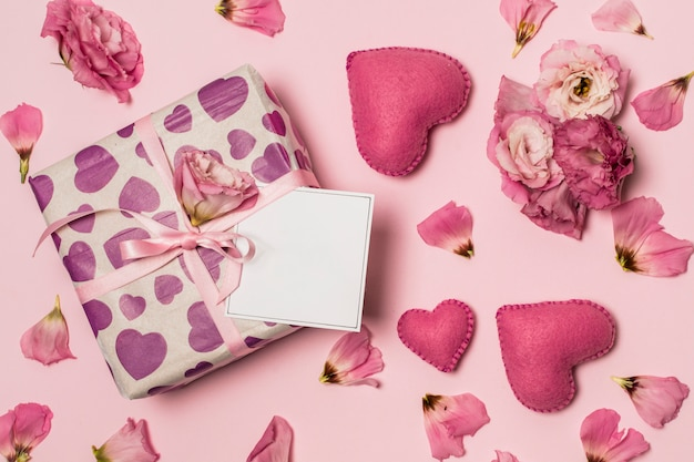 Papel no presente perto de corações, flores e pétalas