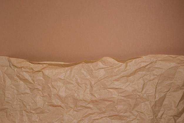 Papel ofício amassado em um fundo de papelão marrom.