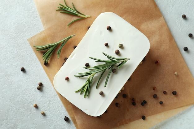 Papel para assar com queijo feta, pimenta e alecrim em superfície texturizada branca