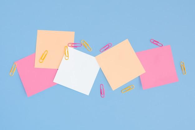 Papel para cartas e clipes de papel em um fundo azul
