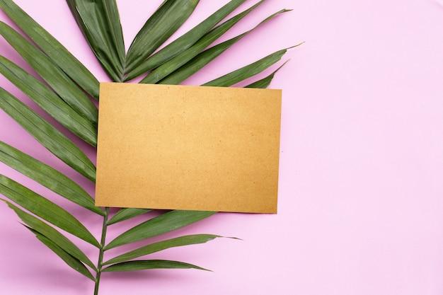 Papel pardo em branco em folhas de palmeira tropical na superfície rosa