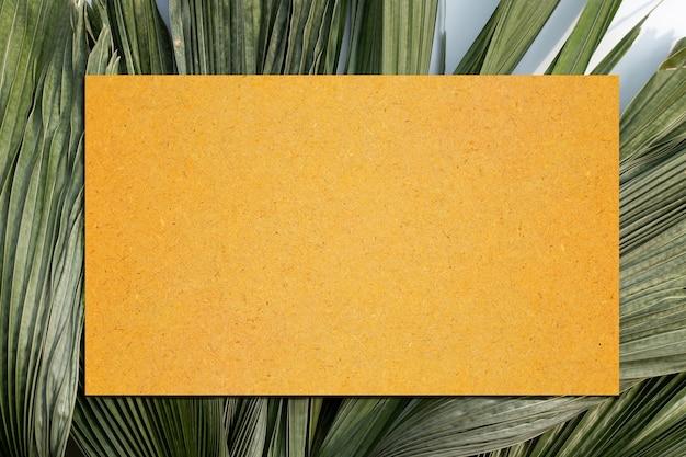 Papel pardo em branco nas folhas secas da palmeira tropical. copie o espaço