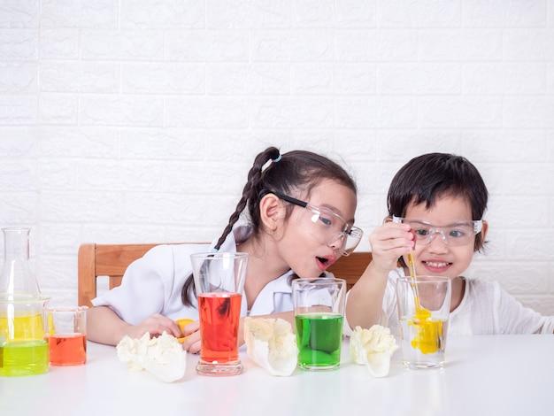 Papel pequeno asiático da menina dois bonito que joga um cientista. o experimento da água transpota com cores para o repolho. o primeiro passo é soltar corante na água. aprendizagem e educação do garoto.