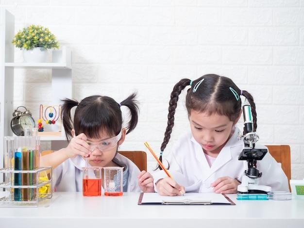 Papel pequeno da menina do irmão dois asiáticos que joga um cientista no laboratório de ciência com equipamento. aprendizagem e educação do garoto.