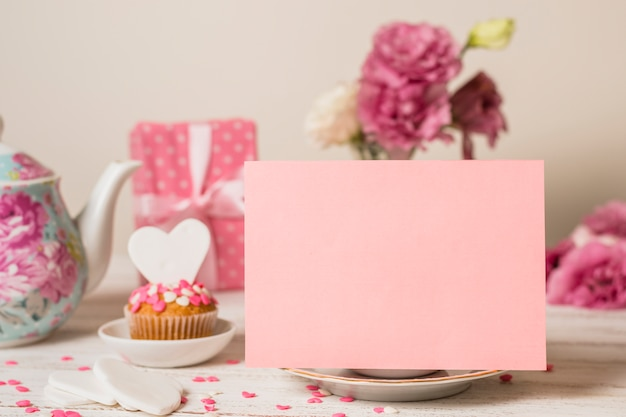 Papel perto de bolo delicioso, caixa de presente e bule