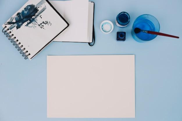 Papel perto de cadernos de esboços e tinta