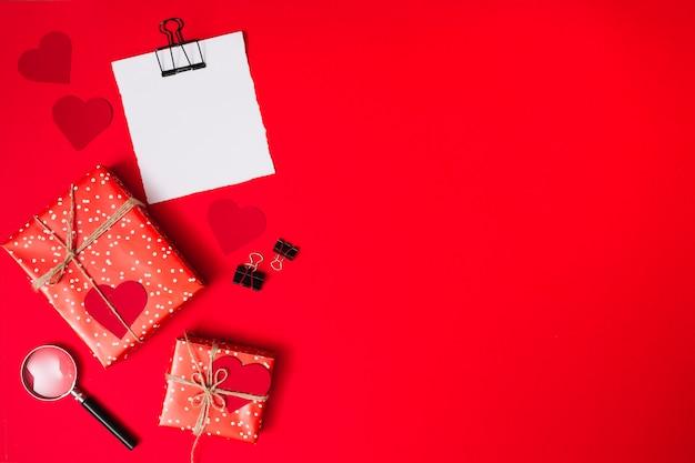 Papel perto de caixas de presentes com corações ornamento, clipes e lupa