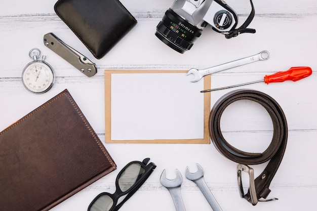 Papel perto de câmera, notebook, cronômetro, equipamentos de reparo e pulseira de couro
