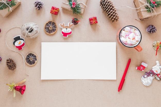 Papel perto de caneta, copo e decorações de natal