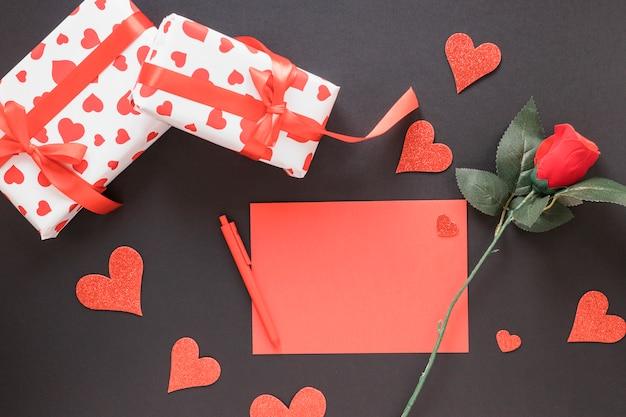 Papel perto de caneta, ornamento corações, flores e presentes