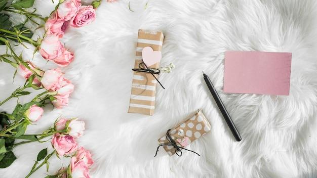 Papel perto de caneta, presentes e flores frescas em colcha de lã