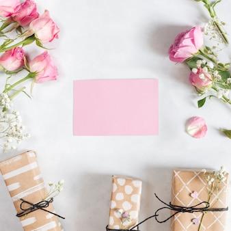 Papel perto de lindas rosas e presentes