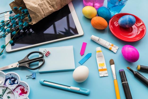 Papel perto de ovos de páscoa, galhos de salgueiro em tablet e artigos de papelaria