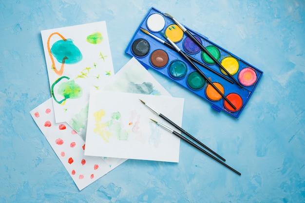 Papel pintado à mão e suprimentos de pintura sobre o plano de fundo texturizado azul