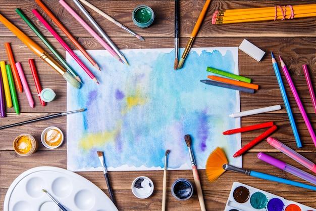 Papel pintado, pincéis, tintas, lápis de cor e papelaria em prosa