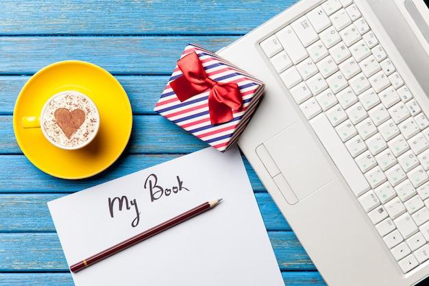 Papel, presente, café e laptop deitado na mesa