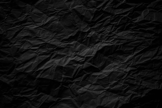 Papel preto escuro amassado close-up do fundo da textura
