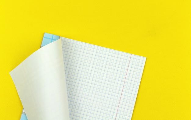 Papel quadriculado de caderno escolar, fundo plano simples de conceito de educação com mesa de escritório amarela, foto de vista superior