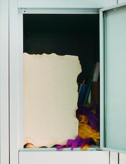 Papel queimado e boa de penas no armário aberto