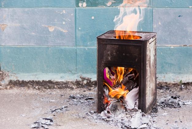 Papel queimado em caixa de aço com chamas de fogo frente da parede