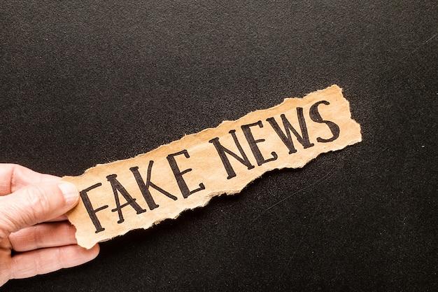 Papel rasgado com texto fake news