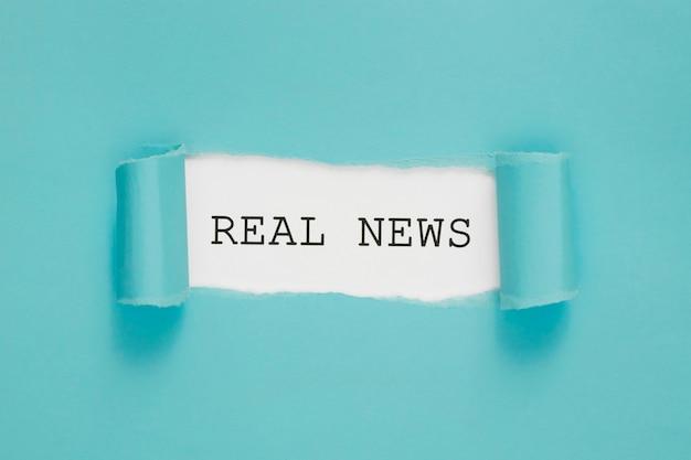 Papel rasgado de notícias reais na parede azul e branca