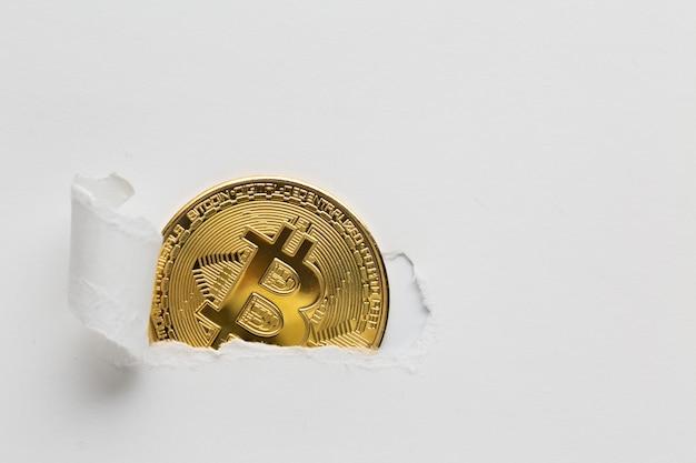 Papel rasgado revelando bitcoin