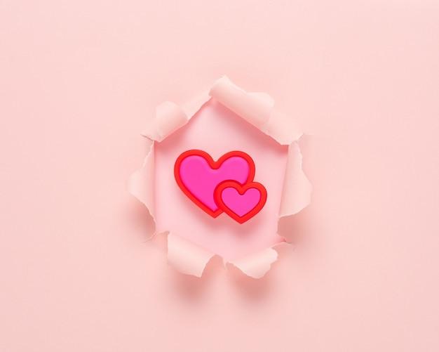 Papel rasgado rosa vivo com coração na superfície rosa.
