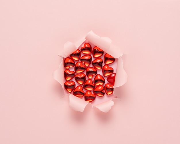 Papel rasgado rosa vivo com corações de vidro vermelho na superfície rosa.