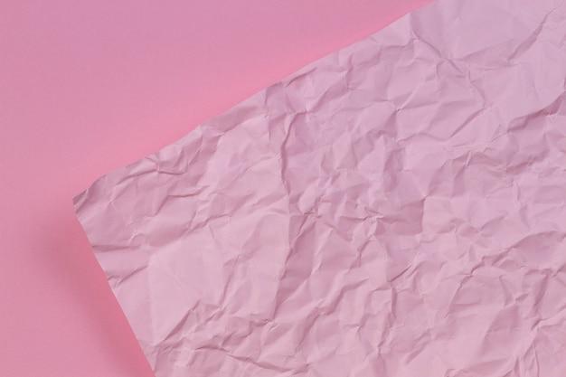 Papel rosa amassado amassado sobre fundo de textura de papel rosa em branco