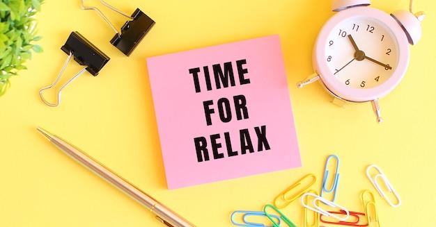 Papel rosa com a inscrição hora para relaxar. relógio, caneta sobre um fundo amarelo. conceito de design.