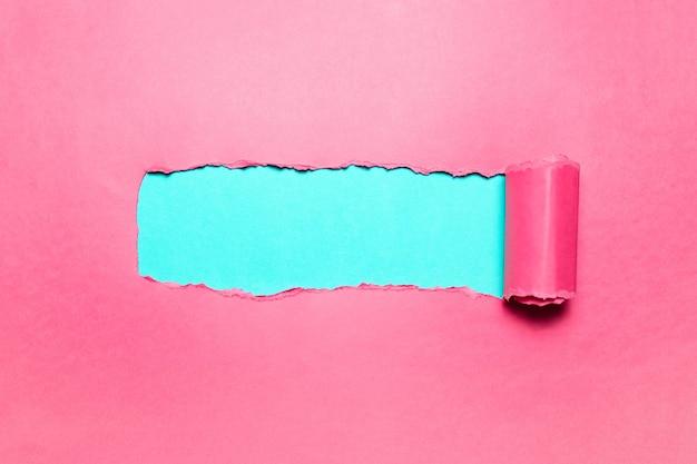 Papel rosa rasgado diagonalmente com espaço para texto de fundo ciano.