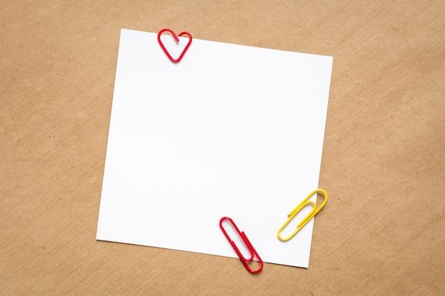 Papel timbrado branco e clipes de papel coloridos em fundo de papel kraft