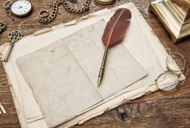 Papel usado vintage com caneta de pena. suprimentos e acessórios de escritório antigos na mesa de madeira