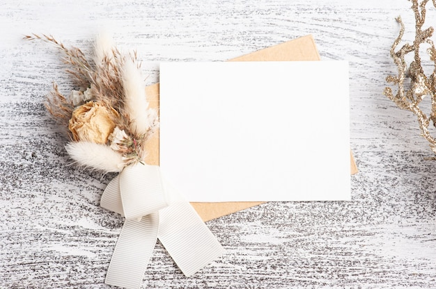 Papel vazio e envelope kraft com buquê de flores secas de cores neutras. simulação de casamento na mesa branca