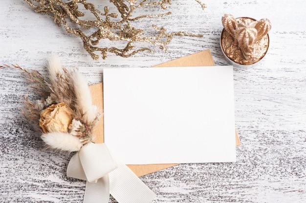 Papel vazio e envelope kraft com buquê de flores secas de cores neutras. suculenta dourada e decoração em mesa branca. espaço de trabalho moderno