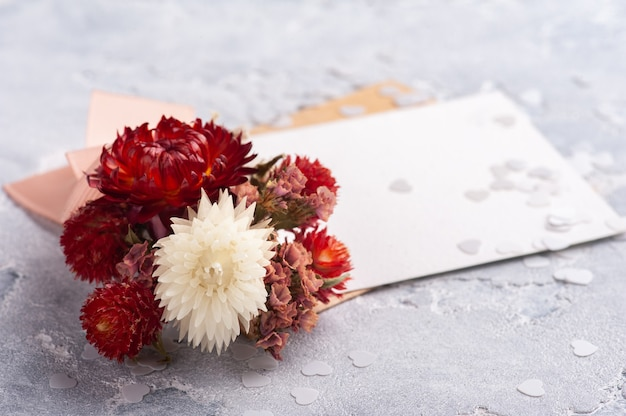 Papel vazio e envelope kraft com buquê vermelho de flores secas. simulação de casamento na mesa cinza