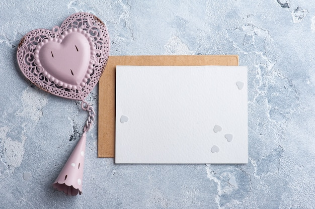 Papel vazio e envelope kraft com coração decorativo rosa. simulação de casamento na mesa cinza